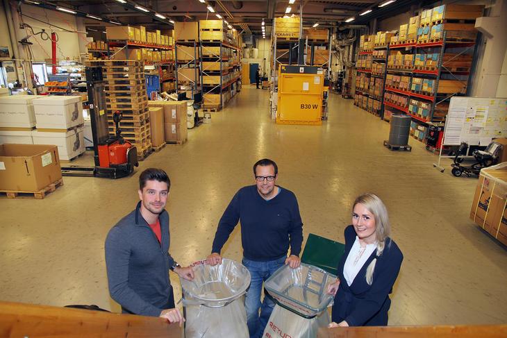 Tre personer i et lagerlokale