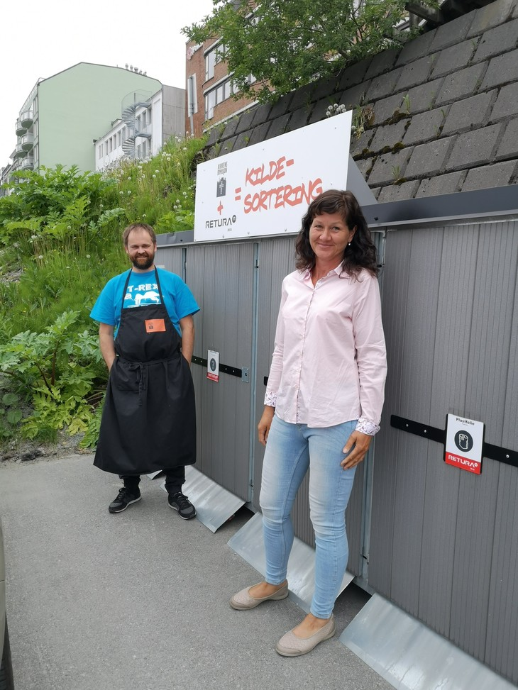 To personer foran skap til avfallsdunker